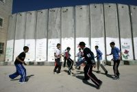 Palestinian boys playing soccer against the backdrop of the Israeli separation barrier that bisects their school playground in East Jerusalem, 2006
