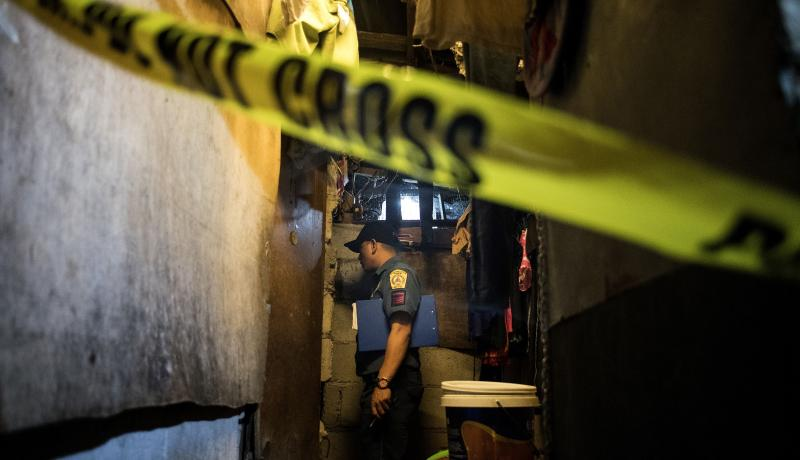 A policeman in Manila investigates the scene where the body of an alleged drug user lies after being killed by unidentified assailants on 8 December 2017. Photo: Getty Images.