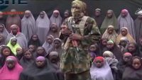 In this undated image taken from video distributed Aug. 14, 2016, an alleged Boko Haram soldier standing in front of a group of girls alleged to be some of the 276 abducted Chibok schoolgirls held since April 2014, in an unknown location. (Militant video/Site Institute/AP)