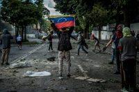 Un manifestante sostiene una bandera de Venezuela después de una confrontación con soldados durante una protesta en Caracas el 26 de julio de 2017. Credit Meridith Kohut para The New York Times