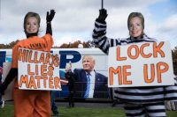 People in prison garb wearing Hillary Clinton masks outside a Trump campaign event in 2016. Credit Damon Winter/The New York Times