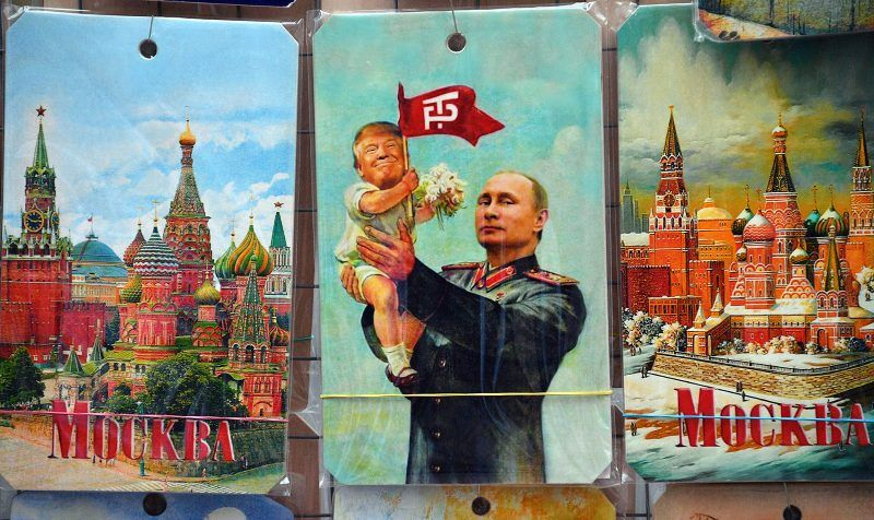 """A picture taken on July 5, 2017 shows a souvenir kiosk offering among others a drawing depicting Russian President Vladimir Putin holding a baby with the face of US President Donald Trump, based upon a propaganda poster showing late soviet leader Joseph Stalin holding a baby, in Moscow. It was a constant refrain on the campaign trail for Donald Trump in his quest for the US presidency: """"We're going to have a great relationship with Putin and Russia."""" Now, weighed down by claims that Moscow helped put him in the White House, Trump is set to finally meet his Russian counterpart in an encounter fraught with potential danger for the struggling American leader. / AFP PHOTO / Mladen ANTONOV (Photo credit should read MLADEN ANTONOV/AFP/Getty Images)"""