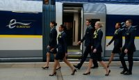 Staff members walk past a Eurostar e320 train at St. Pancras station in London. Credit Alastair Grant/Associated Press