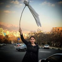 A young Iranian woman waves a white headscarf in protest of her country's compulsory hijab rule.