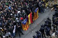 Catalan regional police officers block the way as protesters, holding pro-independence and republican flags, try to reach the Spanish government office in Barcelona on March 25. The protests were held after Carles Puigdemont, the fugitive ex-leader of Catalonia and ardent separatist, was arrested Sunday by German police on an international warrant. (Emilio Morenatti/AP)