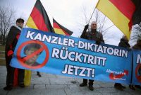 """Sean Gallup/Getty Images Supporters of Germany's far-right AfD party holding a banner that reads, """"Chancellor-Dictator Resignation Now!"""" on the day that Chancellor Angela Merkel was narrowly elected for a fourth term, Berlin, March 14, 2018"""