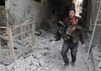 EDITORS NOTE: Graphic content / A Syrian man rescues a child following a reported regime air strike in the rebel-held town of Hamouria, in the besieged Eastern Ghouta region on the outskirts of the capital Damascus on February 21, 2018. / AFP PHOTO / ABDULMONAM EASSA (Photo credit should read ABDULMONAM EASSA/AFP/Getty Images)