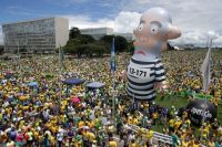 Protesters demand the impeachment of Dilma Rousseff, then the president of Brazil, during a March 2016 rally in Brasilia. A large inflatable doll depicts former president Luiz Inácio Lula da Silva, her mentor, in prison garb. Rousseff was ousted later that year amid a bribery scandal. (Eraldo Peres/AP)