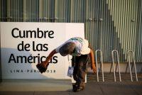Una mujer limpia una señalización de la Cumbre de las Américas en Lima, Perú, el 10 de abril de 2018. Credit Iván Alvarado/Reuters