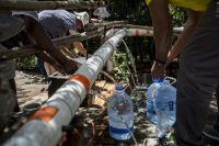 People refill water bottles at the Newlands spring tap, a fresh mountain spring that runs through Cape Town, South Africa, on Feb. 14. (Charlie Shoemaker for The Washington Post)