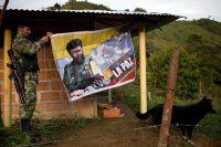 Un miembro de las Farc cuelga un cartel del líder fallecido de la guerrilla Alfonso Cano en Colombia, en enero de 2016. Credit Rodrigo Abd/Associated Press