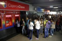 Customers wait in line at an ATM outside a Banco de Venezuela branch in Caracas, Venezuela, on March 23. (Marco Bello/Reuters)