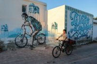 A Tunisian boy cycles past street art in Erriadh, a village on the resort island of Djerba, south of Tunis in 2015. (Mosa'ab Elshamy/AP)
