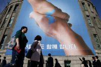 Pedestrians in Seoul, South Korea, in front of a banner supporting unity between the North and South at a summit scheduled for April 27.CreditChung Sung-Jun/Getty Images