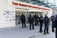 """Riot police officers stand in front of a broken shop window and writings reading in French """"legitimate or not, our anger in your face"""" during clashes on the sidelines of a demonstration on April 19, 2018 in Paris, as part of a multi branch day of protest called by French unions CGT and Solidaires against French President's policies amid a rail strike and spreading student sit-ins. (Photo by Michel Stoupak/NurPhoto via Getty Images)"""