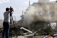 During a press tour organized by the Syrian information ministry, a journalist films the wreckage of a building described as part of the scientific studies and research center compound in the Barzeh district, north of Damascus. (Louai Beshara)