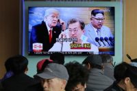 "In a photo from March, people at a rail station in Seoul watch a TV screen showing images of North Korean leader Kim Jong Un, right, South Korean President Moon Jae-in, center, and President Trump. Korean letters on the screen read: ""Thawing Korean Peninsula."" (AP Photo/Ahn Young-joon, File)"