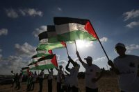 Palestinians hold their national flag at the site of protests on the Israel-Gaza border in the northern Gaza Strip. (AFP/Getty Images)