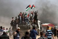 Palestinians wave flags as smoke billows from burning tires at the Israeli-Gazan border Friday. (Mahmud Hams/AFP/Getty Images)