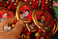 A woman selects a souvenir necklace with a portrait of Chinese President Xi Jinping at a stall in Tiananmen Square in Beijing, China. Feb. 26, 2018. (Thomas Peter/Reuters)