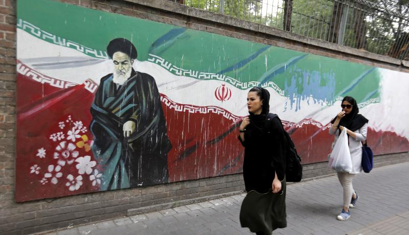 An Iranian woman walks past a mural on the wall of the former US embassy in Tehran. Photo: Getty Images.