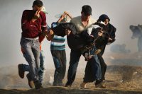 People run through tear gas May 15 carrying an injured woman at the border fence with Israel in Gaza City, Gaza. (Spencer Platt/Getty Images)