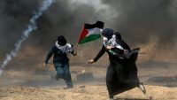 Female demonstrators run for cover from tear gas fired by Israeli forces during a protest where Palestinians demand the right to return to their homeland, at the Israel-Gaza border in the southern Gaza Strip on 11 May 2018 REUTERS/Ibraheem Abu Mustafa
