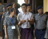 Reuters journalist Wa Lone, center, is escorted in handcuffs by police upon arrival at his trial on Wednesday in Rangoon, Burma. (Thein Zaw/AP)