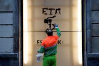 Un trabajador municipal remueve un grafiti en Bilbao a favor de ETA, dos días después de que la banda separatista anunciara su disolución. Credit Vincent West/Reuters