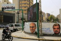 A poster of the Koullouna Watani list, left top, and other posters for parliamentary elections that include a portrait of assassinated Lebanese prime minister Rafiq Hariri, right, are displayed in Beirut, on Tuesday. (Hassan Ammar/AP)
