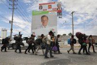 Un grupo de migrantes de Centroamérica pasa por carteles de las campañas electorales en Hermosillo, México, el 21 de abril de 2018. Credit John Moore/Getty Images