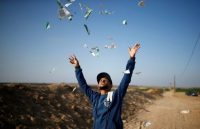 A Palestinian man throws leaflets dropped by the Israeli military during a protest against the U.S. Embassy move to Jerusalem on May 14. (Mohammed Salem/Reuters)