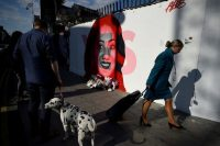 An Aer Lingus flight attendant walks past a new mural of Savita Halappanavar in Dublin on Friday, the day of a referendum on liberalizing Ireland's abortion laws. Halappanavar's death after a miscarriage helped spur the referendum. (Clodagh Kilcoyne/Reuters)