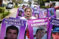 A woman holds banners with the pictures of missing persons during a march to mark Mother's Day in Xalapa, in the state of Veracruz, on May 10. (Photo: Yahir Ceballos/Reuters)