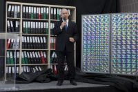 Israeli Prime Minister Benjamin Netanyahu stands in front of a shelf of files and discs he said were copies of documents Israel obtained from Iran's secret nuclear archive. (Sebastian Scheiner/AP)