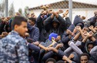 Des migrants africains lèvent les bras pour protester contre leur détention, réclamant leur transfert vers l'Europe, au sud de Tripoli, le 2 février. Photo Mahmud Turkia. AFP