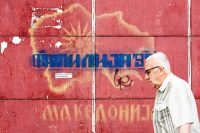 A man passes in front of a graffiti with an old map of Macedoni in Skopje on Wednesday.CreditRobert Atanasovski/Agence France-Presse — Getty Image