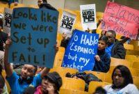 El estudiante Magdiel González, durante una protesta a finales de 2017 en la escuela Arturo Toscanini, en el Bronx de Nueva York, sostiene el cartel azul en español en el que advierte que habla español, aunque no sus maestros. Credit Joshua Bright para The New York Times