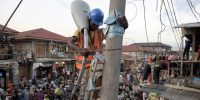 A volunteer sets up a street lamp in the market area of the Oshodi district in Lagos. PIUS UTOMI EKPEI/AFP/Getty Images