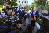 Janez Jansa, right-wing opposition Slovenian Democratic Party leader, right, speaks after casting his ballot at a polling station in Ljubljana, Slovenia, on Sunday. (AP)