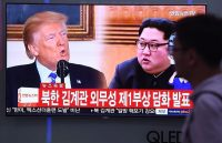 A man walks past a television news screen showing North Korean leader Kim Jong Un (R) and US President Donald Trump (L) at a railway station in Seoul on May 16, 2018. - North Korea threatened on May 16, to cancel the forthcoming summit between leader Kim Jong Un and President Donald Trump if Washington seeks to push Pyongyang into unilaterally giving up its nuclear arsenal. (Photo by Jung Yeon-je / AFP) (Photo credit should read JUNG YEON-JE/AFP/Getty Images)