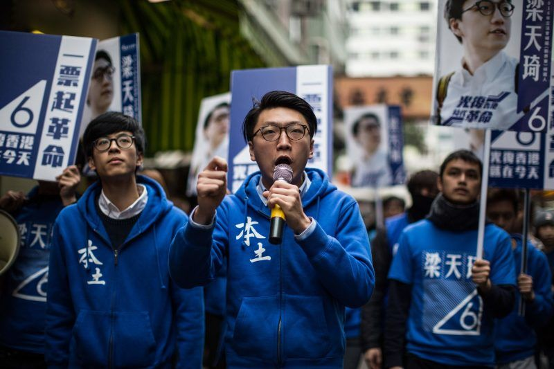 """Edward Leung, center, shown in 2016, is a leading independence activist now serving a six-year prison sentence for """"rioting.""""CreditAnthony Wallace/Agence France-Presse — Getty Images"""