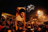 In this May 14 photo, supporters of Shiite cleric Muqtada al-Sadr carry his image as they celebrate in Baghdad's Tahrir Square. (Hadi Mizban/Associated Press)