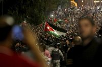 Jordanian protesters shout slogans and raise a national flag during a demonstration outside the prime minister's office in the capital, Amman, on June 4. (Raad Adayleh/AP)