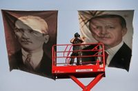 A Turkish police officer watches a political rally in Istanbul in front of posters of the founder of the Turkish Republic, Mustafa Kemal Ataturk, left, and the current president, Recep Tayyip Erdogan. (Lefteris Pitarakis/AP)