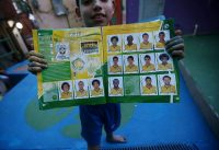 A boy from Santa Marta favela with his Panini World Cup sticker book, Rio de Janeiro, Brazil, 2014. Mario Tama/Getty Images.