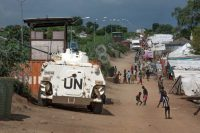 Civilians sheltering in a U.N. base in South Sudan's capital of Juba walk by an armored vehicle and a watchtower manned by Chinese U.N. peacekeepers. (Jason Patinkin/AP)