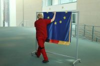 A worker rolls away flags, including those of Germany and the European Union, at the Chancellery in Berlin in April.CreditSean Gallup/Getty Images