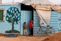 Syrian refugee children stand in front of their home at Al Zaatari refugee camp, in the Jordanian city of Mafraq near the border with Syria, in February. (Muhammad Hamed/Reuters)