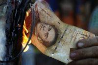 Una persona le prende fuego a un billete de cien bolívares durante una protesta en diciembre de 2016. Credit Carlos Eduardo Ramírez/Reuters